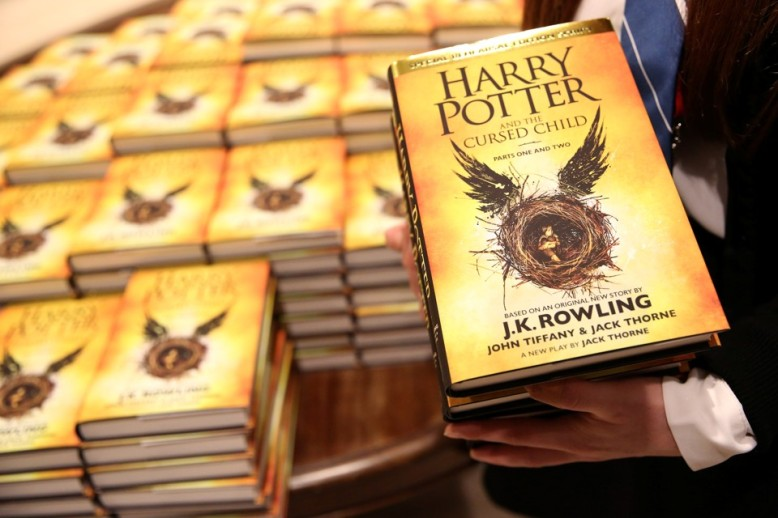 A store assistant holds copies of the book of the play of Harry Potter and the Cursed Child parts One and Two at a bookstore in London